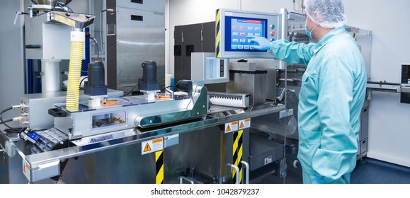 Pharmacy industry factory man worker in protective clothing in sterile working conditions operating on pharmaceutical equipment