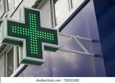 Pharmacy Neon Sign. Green ?ross sign on the building. Pharmacy concept. Drug store.