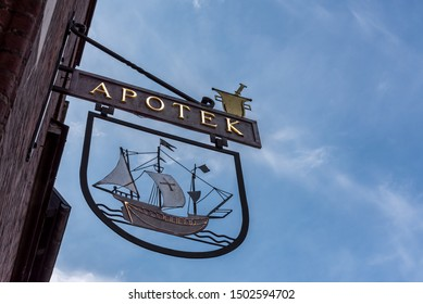 pharmacy sign showing a ship and a mortar against blue sky, Svendborg, Denmark, 11 July 2019