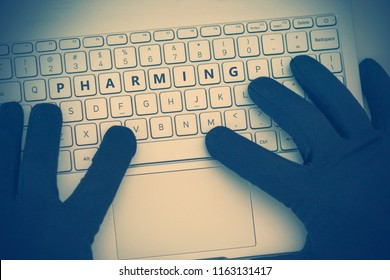 PHARMING inscription on laptop keyboard. Hacker man using a laptop attacks the web. Cyberattack, online theft of personal data and cybercrime concept