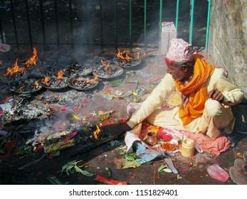 Pharping, Nepal - November 26, 2005: Unidentified Nepali man wearing traditional dress burns candles in Dakshinkali Hindu temple in Pharping, Nepal.