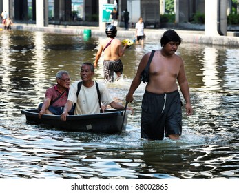 PHATHUMTRANI, THAILAND- OCTOBER 21: Men use boat as a transportation through water during the worst flooding in decades on October 21, 2011 Rongsit Road, Phathumtrani, Thailand.