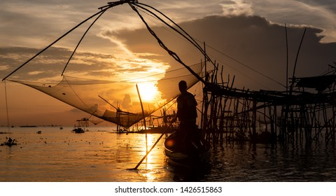 Phatthalung, Thailand, 28.05.2019 - A fisherman on his boat on the Thale Noi lake in south Thailand