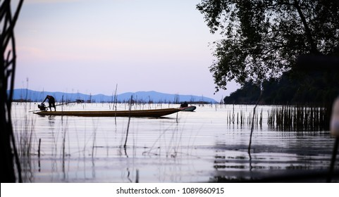 Phatthalung, Thailand April 3, 2018  people silhouettes in boats in river.