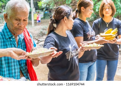 PHATTHALUNG, THAILAND - April 8, 2018 : People are stand in line for transfer food by hand to hand cross the  Klong Ban Kham canal in the forest at Srinagarindra District, Phatthalung.