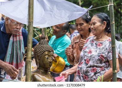 PHATTHALUNG, THAILAND - April 8, 2018 : People are shower the buddha sculpture for cerebrate Songkran festival at Klong Ban Kham in the forest at Srinagarindra District, Phatthalung.