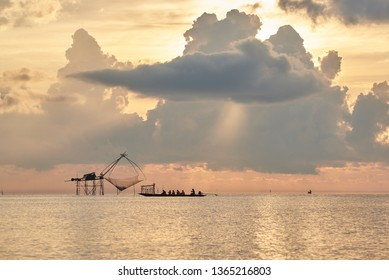 Phatthalung, Thailand- April 9, 2019: Tourists on the longtail boat taking photography of Yor, net fishing of fishermen, during sunrise in the morning at Pakpra, Phatthalung, Thailand.
