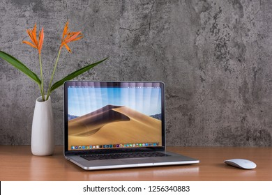 PHATTHALUNG, THAILAND - December 1, 2018: Macbook computers, magic mouse and flowers vase on wooden table, created by Apple Inc.