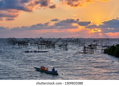 Phatthalung, Thailand- February 11, 2019: Tourists on the long tail boat taking photography of Yor, net fishing of fishermen, during sunrise in the morning at Pakpra, Phatthalung, Thailand.