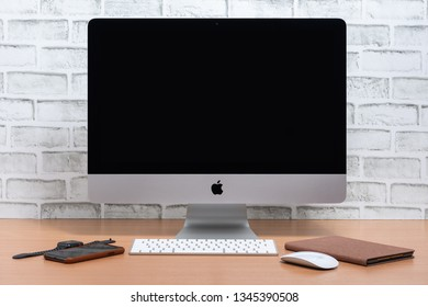 PHATTHALUNG, THAILAND - March 1, 2019 : iMac computer, iPad mini, iPhone X and Apple Watch on wooden table with white brick wall