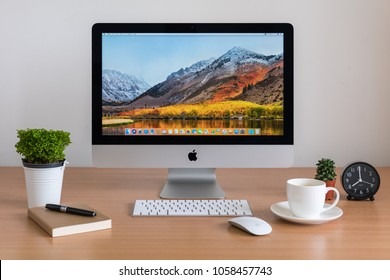 PHATTHALUNG, THAILAND - MARCH 24, 2018: iMac monitor computers, keyboard and magic mouse on wooden table, created by Apple Inc.