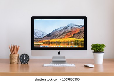 PHATTHALUNG, THAILAND - MARCH 24, 2018: iMac computer, keyboard, magic mouse, plant vase, clock and pencils on wooden table, created by Apple Inc.