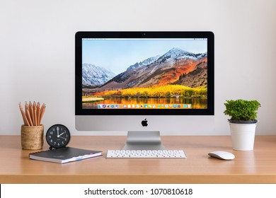 PHATTHALUNG, THAILAND - MARCH 24, 2018: iMac computer, keyboard, magic mouse, plant vase, clock, note book and pencils on wooden table, created by Apple Inc.