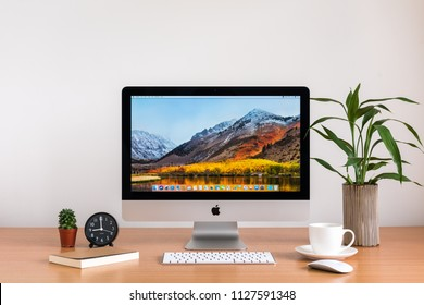 PHATTHALUNG, THAILAND - MARCH 24, 2018: iMac monitor computers, keyboard and magic mouse, coffee cup, cactus, note book, tree vase on wooden table, created by Apple Inc.