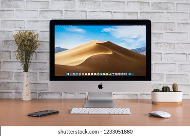 PHATTHALUNG, THAILAND - November 18, 2018: iMac monitor computers,  keyboard, magic mouse, iPhone, dry flowers and cactus vase on wooden table, created by Apple Inc.