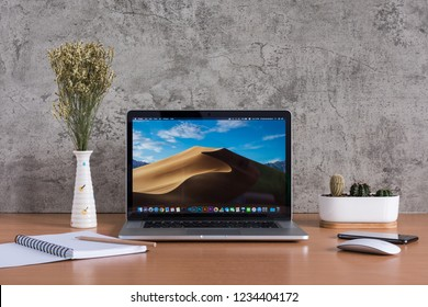 PHATTHALUNG, THAILAND - November 18, 2018: Macbook computers, note book, pencil,  magic mouse, iPhone, dry flowers and cactus vase on wooden table, created by Apple Inc.