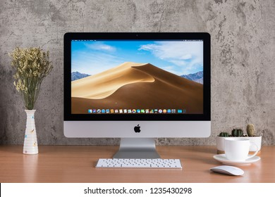 PHATTHALUNG, THAILAND - November 18, 2018: iMac monitor computers,  keyboard, magic mouse, dry flowers, coffee cup and cactus vase on wooden table, created by Apple Inc.