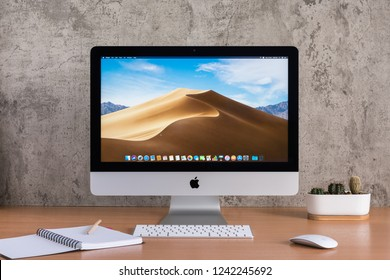 PHATTHALUNG, THAILAND - November 18, 2018: iMac monitor computers,  keyboard, magic mouse, note book, pencil and cactus vase on wooden table, created by Apple Inc.