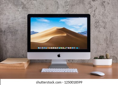 PHATTHALUNG, THAILAND - November 18, 2018: iMac monitor computers,  keyboard, magic mouse, old book and cactus vase on wooden table, created by Apple Inc.