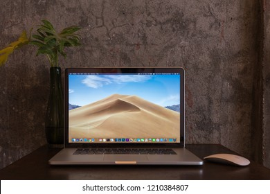 PHATTHALUNG, THAILAND - October 14, 2018: MacOS Mojave on screen of  Apple Macbook pro computer with magic mouse on rustic table, Loft style wall, created by Apple Inc.