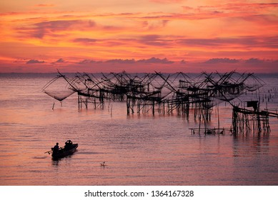 Phatthalung/Thailand- April 9, 2019: Tourists on the long tail boat taking photography of Yor, net fishing of fishermen, during sunrise in the morning at Pakpra, Phatthalung, Thailand.