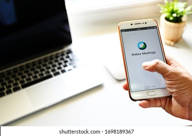 Phatthalung,Thailand-April 07,2020. Business man using Webex Meetings mobile app in home Office video conferencing Meetings,of popular online conference application.WORK FROM HOME
