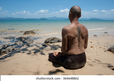 Phayam Island, Thailand - March 18, 2014: Buddhist monk meditating on the beach by the sea on a nice sunny weather, alone, pose yoga, naked torso