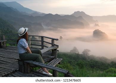 PHAYAO, THAILAND-10 OCTOBER 2018: A woman sit alone at wooden balcony of cafe to see scenic view of mountain and mist in sunrise at Phu lang ka national park, Phayao, Thialand