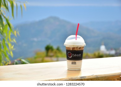 Phetchabun, Thailand​ - January​ 05, 2019​: Coffee in white cup with nature view behind in Khao Kho, Takmoh coffee​ shop, Phetchabun, Thailand.