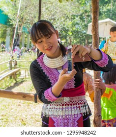 Phetchabun, Thailand – December 16, 2018 Countryside festival in Hmong village, happy girl taking pictures with smartphone