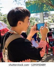 Phetchabun, Thailand – December 16, 2018 Countryside festival in Hmong village, happy young man taking pictures with smartphone