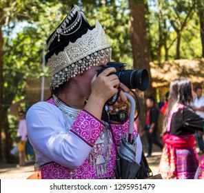 Phetchabun, Thailand – December 16, 2018 Countryside festival in Hmong village, happy girl taking pictures with digital camera
