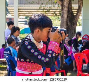 Phetchabun, Thailand – December 16, 2018 Countryside festival in Hmong village, happy young man taking pictures with digital camera