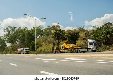 Phetchabun, THAILAND – January 31, 2018 Lowboy semi-trailer carrying vibratory soil compactor and freight bulk cement tank semi-trailer transporting powder cement on the Asian highway