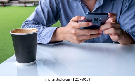 Phetchabun, Thailand - June 4th 2018 : A man wearing gray shirt use smartphone blue Samsung S9 plus and a cup of hot coffee on white table.
