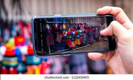 Phetchabun, Thailand - June4th 2018 a man holding smartphone on hand with show screen of colorful homespun clothes and stuff thing made from local fabric ready to take photo by Samsung galaxy S9 plus.