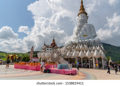 Phetchabun, Thailand-14 October 2019 : Five white Buddha statue sequences on the state among tourist to make merit, cloudy, blue sky at Wat Pha Sorn Kaew (Temple on the Glass Cliff)