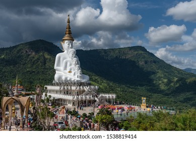 Phetchabun, Thailand-14 October 2019 : Five white Buddha statue sequences on the state among cloudy, blue sky and hill as background at Wat Pha Sorn Kaew (Temple on the Glass Cliff)