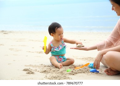 PHETCHABURI, THAILAND - AUGUST 28, 2016 : a kid is playing beach sand with her mother on the famous Thailand beach, Cha-um, on their vocation.