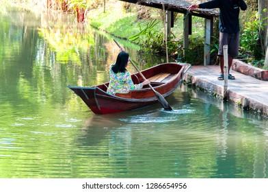 Phetchaburi,Thailand - November 7,2018:Tourists ride the ancient Thai wooden rowing boat. In the garden of Phetchaburi province, Thailand
