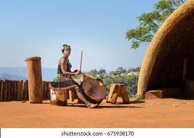 Phezulu village, Botha's Hill, South Africa - August 19, 2013: Zulu woman dressed in traditional gear, plaing the drum in the Valley of a Thousand Hills.