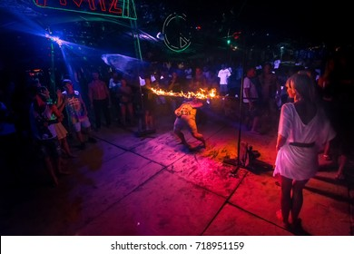 Phi Phi Island, Thailand. Circa September 2017. A tourist limbos under a bar of fire. Crowd partying in Phi Phi Island beach at night.