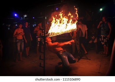 Phi Phi Island, Thailand, November 13, 2017: A merry youth people limbos under a bar of fire. Crowd partying in Phi Phi Island beach dancing the dance of Limbo at night