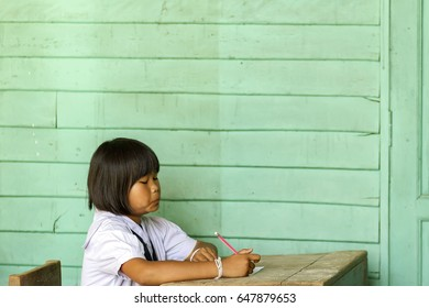 Phichit / Thailand - January 15, 2017: [Thai girl primary student taking a final exam on greenery [pantone color] old wooden classroom at Ban Wang Klom Community School, Wang Krot, Phichit ].