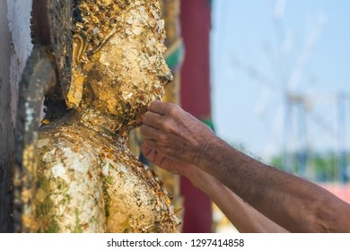 PHICHIT/THAILAND - JANUARY 27, 2019: Hands are paste gold leaf sheet on Buddha images. in Wat Tha Luang at Phichit, Thailand.
