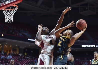 PHILADELPHIA - December 10: Temple Owls guard Daniel Dingle (4) tries to block a shot by a Towson Tigers player during the NCAA basketball game December 10, 2014 in Philadelphia.