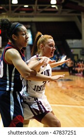 PHILADELPHIA - FEBRUARY 28: St. Joe's women's basketball player Ashley Logue (white jersey) battles for position with Duquesne's Samantha Pollino in the February 28, 2010 game in Philadelphia.