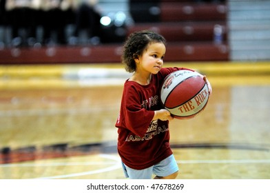 PHILADELPHIA - FEBRUARY 28: A young basketball player heads off St. Joe's court after demonstrating her dribbling skills at halftime of the February 28, 2010 women's basketball game in Philadelphia.