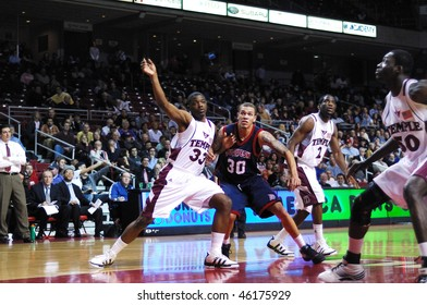 PHILADELPHIA - FEBRUARY 3: Members of the Duquesne and Temple University basketball teams battle for position for a possible rebound in the February 3, 2010 game in Philadelphia.