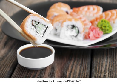 Philadelphia Maki on a black plate with ginger and wasabi with chopsticks